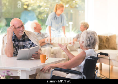 Senior woman in a wheelchair talking to her friend while sitting at a table in common room - Stock Photo