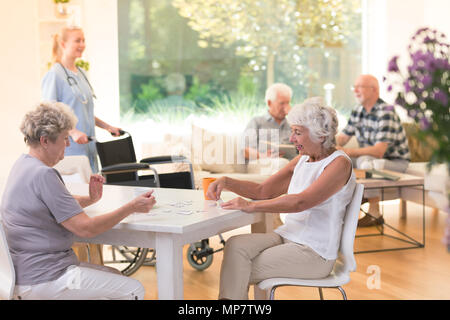 Senior women enjoying their time together while sitting at a table and doing a puzzle in nursing house - Stock Photo