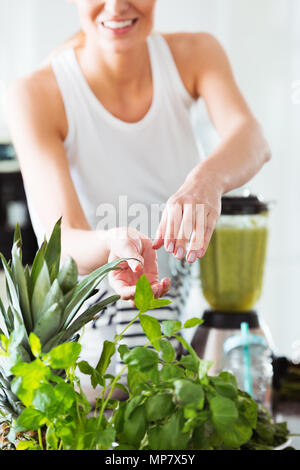 Healthy woman in kitchen preparing vegetable juice in mixer on glossy countertop with carrots - Stock Photo