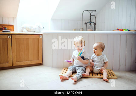 Two toddler children brushing teeth in the bathroom at home. - Stock Photo