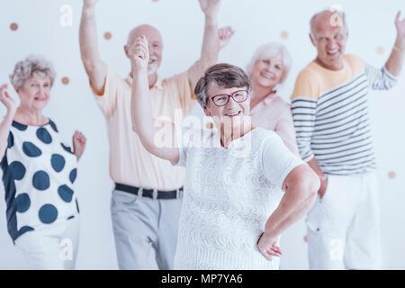 Happy senior woman celebrating birthday with her friends - Stock Photo