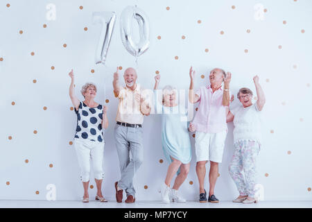 Smiling grandparents enjoying friend's birthday. Couple holding silver balloons against white wall with gold dots - Stock Photo