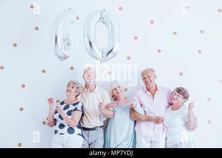 Enthusiastic seniors celebrating elderly woman's birthday with silver balloons - Stock Photo