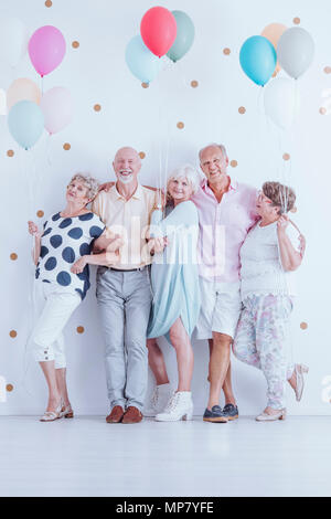 Group of enthusiastic senior friends with colorful balloons celebrating birthday - Stock Photo