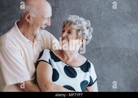 Happy elderly couple celebrating their wedding anniversary against concrete wall - Stock Photo