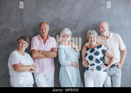 Happy elderly people in casual clothes against concrete wall. Seniors friendship concept - Stock Photo