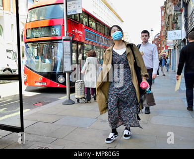 Japanese woman wearing a facemask in Central London, England, UK. - Stock Photo