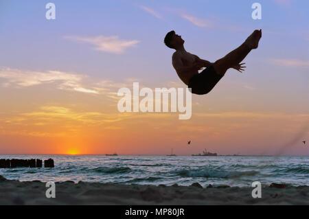 acrobat at sunset of the sea coast, somersault on the beach, acrobatics on the sea - Stock Photo