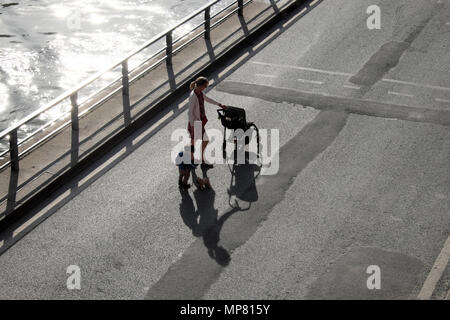 View from above looking down of woman with buggy and toddler with toy puppy dog and shadow walking along the River Seine in Paris France KATHY DEWITT - Stock Photo