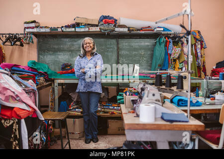 Smiling mature seamstress standing in her busy sewing workshop - Stock Photo