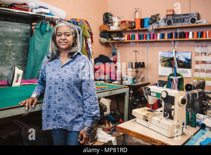 Mature seamstress standing by a table in her sewing workshop - Stock Photo