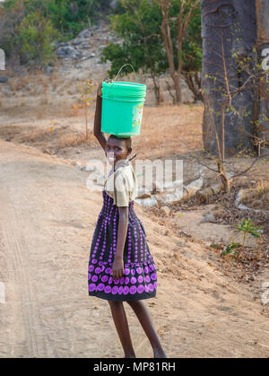 Smiling local young African girl carrying green buckets on her head in an arid area of Likoma Island, Lake Malawi, Malawi, south-east Africa - Stock Photo