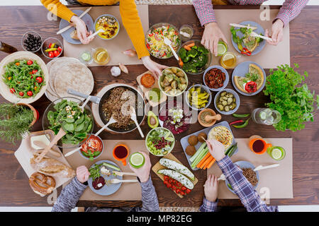 People having veg meal, sitting at wood communal table - Stock Photo