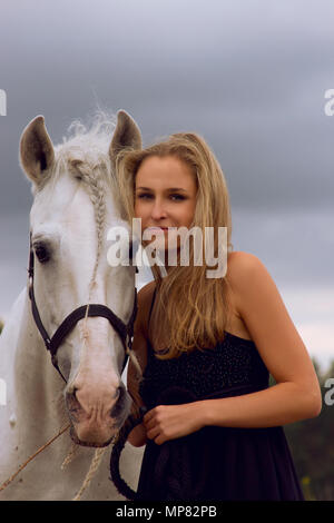 Blond girl with white horse - Stock Photo