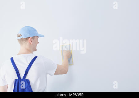Young construction worker preparing the white wall in the house for painting - Stock Photo