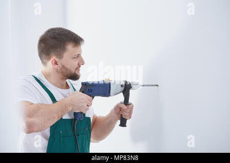 Young specialist in uniform drilling the whole in white wall - Stock Photo