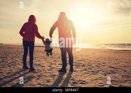 mother and father swinging child by the arms on the beach at sunset - Stock Photo