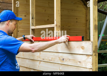 shed construction - worker check the level of wooden plank wall - Stock Photo