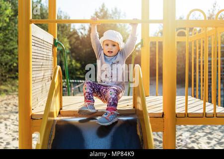 child on slider at playground - Stock Photo