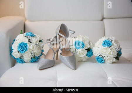 Brides wedding day shiny silver shoes with the bridal bouquet and the bridesmaids bouquets - Stock Photo
