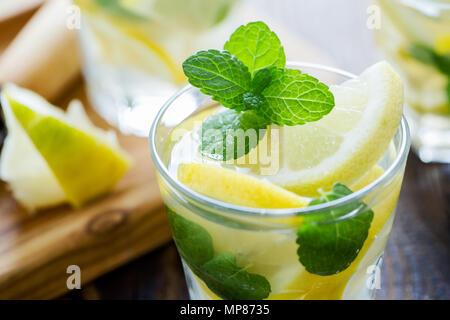Fresh homemade lemonade with lemon slices and fresh mint on wooden table - Stock Photo