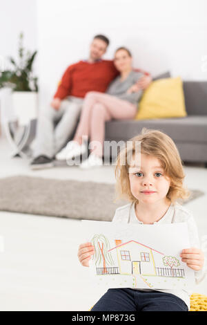 Confused little girl holding a drawing of a house, with her parents sitting on a couch in the blurred backgroud - Stock Photo