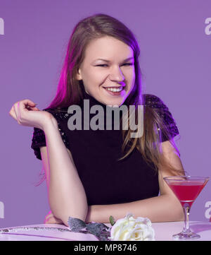 Happy young woman with cocktail at restaurant - Stock Photo