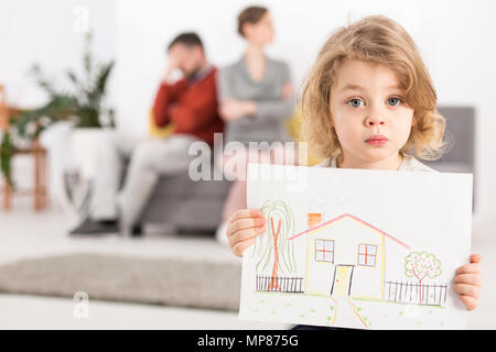 Upset little boy holding a drawing of a house, with his parents sitting angry on a couch in the blurry background - Stock Photo