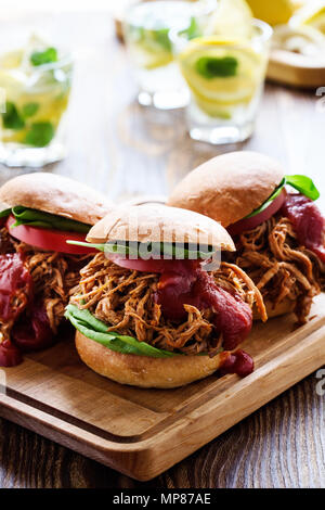 Pulled pork sandwiches with leaf vegetables, tomato on wooden board on picnic table - Stock Photo
