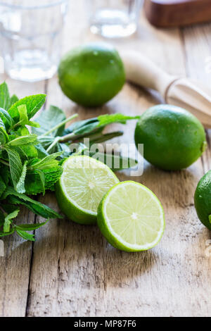 Ingredients for making refreshing summer drink mojito cocktail on rustic wooden table - Stock Photo