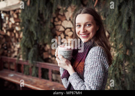 oman wearing warm knit clothes drinking cup of hot tea or coffee outdoors - Stock Photo