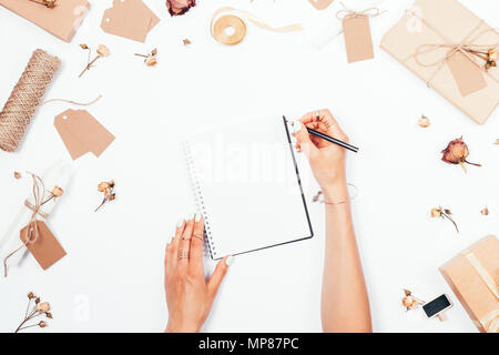 The concept of romantic diary: flat lay arrangement of female hands writing in blank notebook in the center among dried roses, gifts, twine and candle - Stock Photo