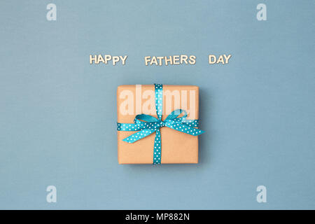 Happy Father's day card with gift box wrapped in kraft paper tied with blue ribbon in polka dots on blue grey background. Greeting card with wooden letters. - Stock Photo