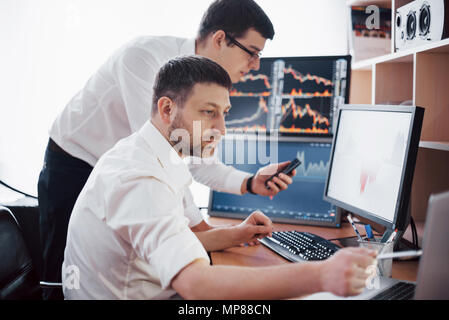 Businessmen trading stocks online. Stock brokers looking at graphs, indexes and numbers on multiple computer screens. Colleagues in discussion in traders office. Business success concept - Stock Photo