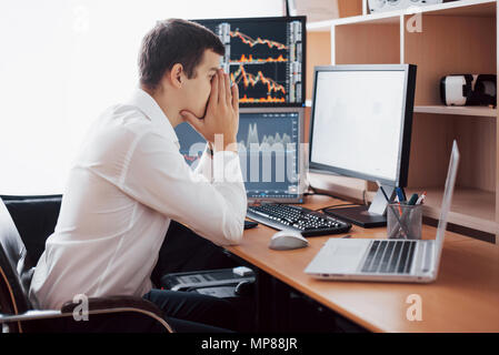 Stressful day at the office. Young businessman holding hands on his face while sitting at the desk in creative office. Stock Exchange Trading Forex Finance Graphic Concept - Stock Photo