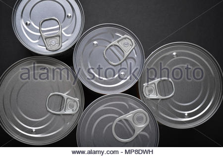 Group of tin cans containing food shot from above on black background - Stock Photo