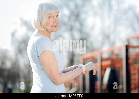 Smiling aged woman showing her fitness tracker