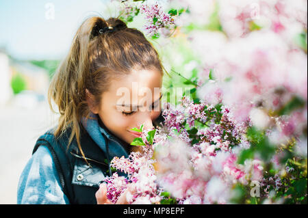 Beautiful, young woman smelling flowers - Stock Photo