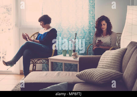 two women friends at home everyone with a mobile phone chat and look or check email. don't speak each other in a modern day. technology destroy friend - Stock Photo