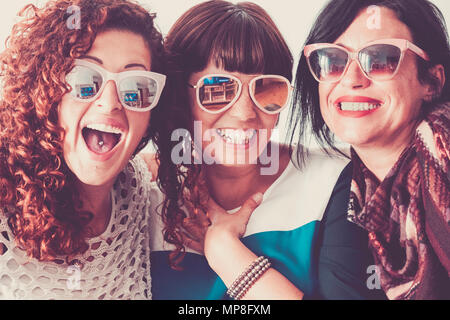 A lot of crazy fun for three women middle age at home wearing sunglasses and big smiles. laughi and happiness for best friends forever doing party ind - Stock Photo