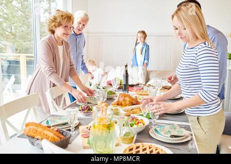 Modern Happy  Family Setting Dinner Table - Stock Photo