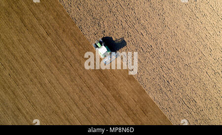 Aerial photo of a tractor ploughing a field in the french countryside - Stock Photo