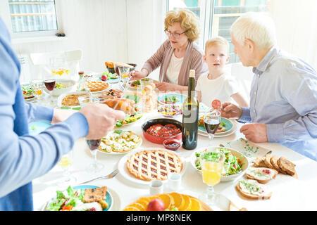 Grandparents Enjoying Family  Dinner in Sunlight - Stock Photo