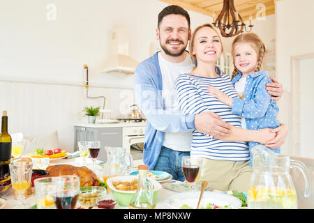 Successful Young Family Posing at Dinner Table - Stock Photo