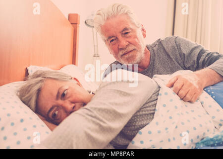 adult mature couple lifestyle waking up after the night. bedroom scene with window natural light. love forever together and nice life concept. white h - Stock Photo