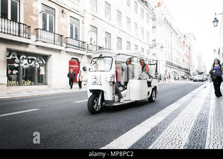 Lisbon, Portugal, May 5, 2018: Tourists are traveling by a traditional tuk-tuk vehicle down a street in downtown Lisbon. - Stock Photo