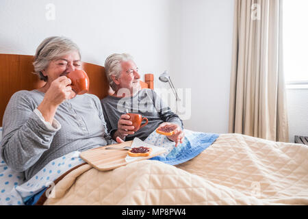 adult people aged couple having fun laughing and smiling on the bed at home. indoor bedroom scene family having brekfast lay down. window light and br - Stock Photo