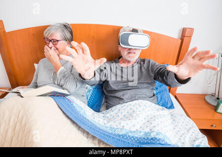 adult people couple having fun in the morning on the bed at home. indoor funny scene with woman that laugh with a book and man using goggles headset w - Stock Photo