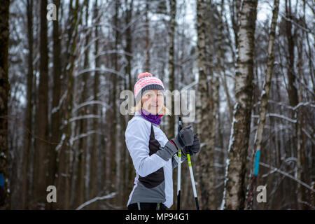 Photo of smiling woman with skis in winter forest - Stock Photo
