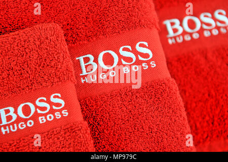 Hugo Boss Logo stitched onto red towels - Stock Photo